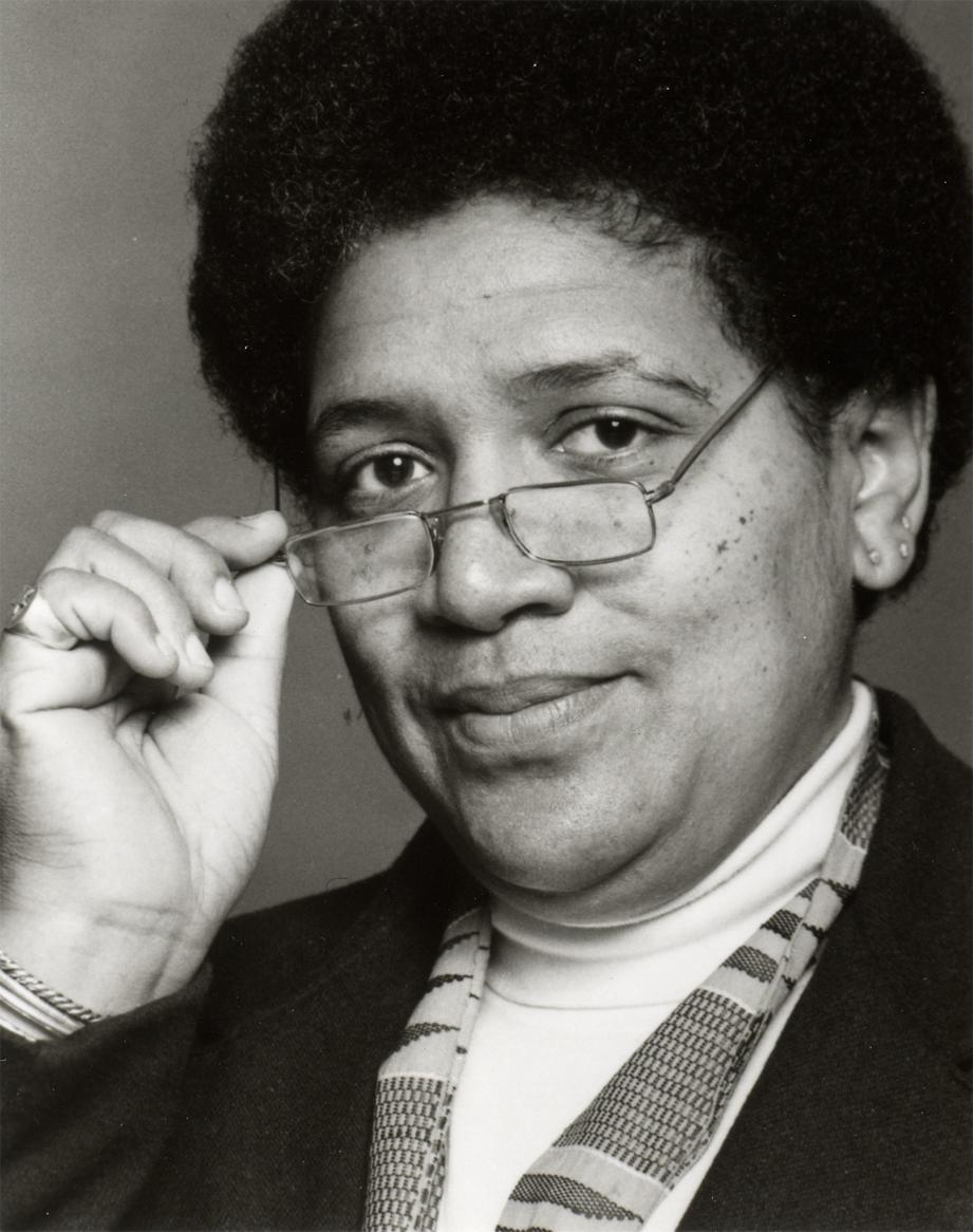 Audre Lorde, female presenting black woman with an afro, holding glasses and looking into the camera