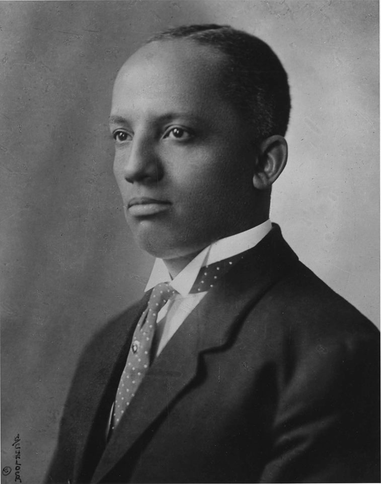 Old black and white photo portrait of black man in suite with tie.