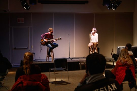 Two musicians, Jackson Peters and Linnea Morris, performing masked and distanced on stage with small audience visible.