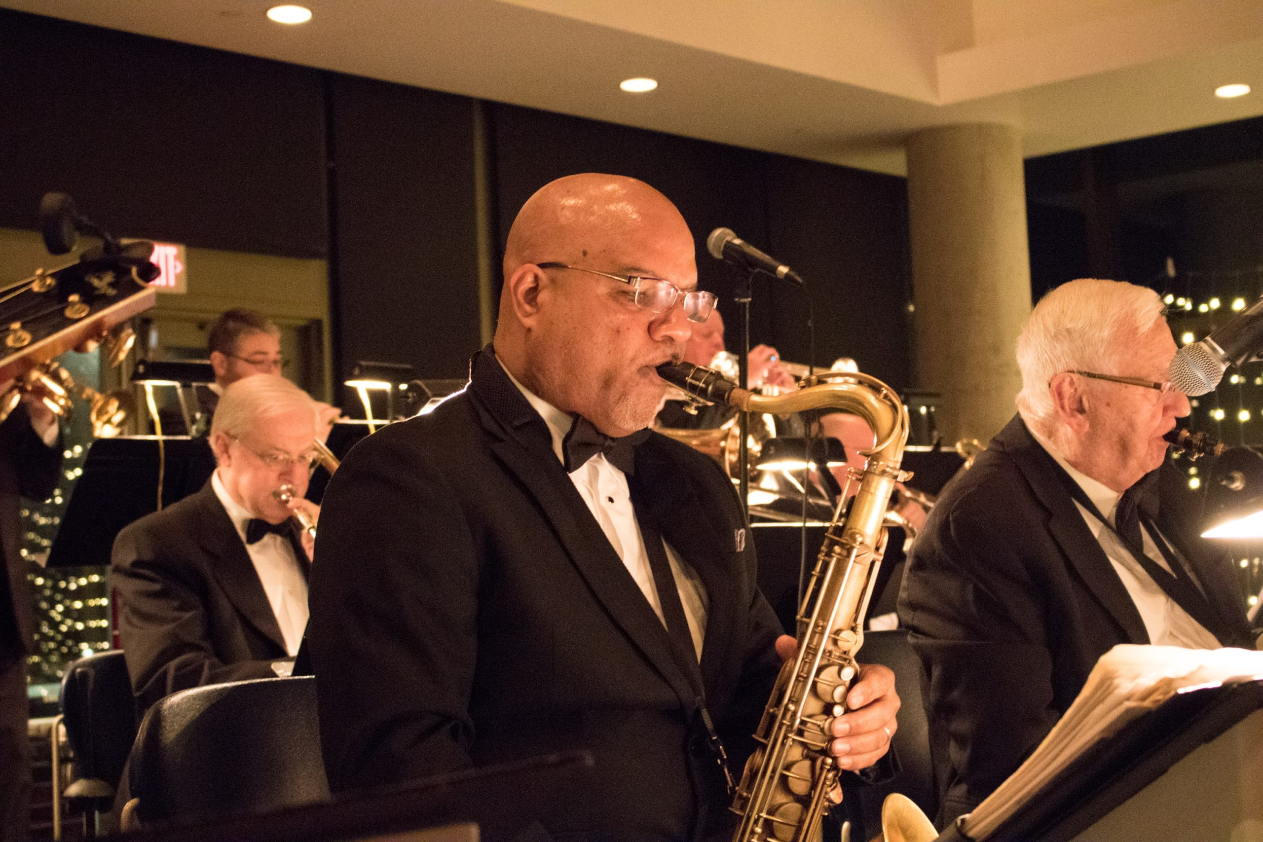Bald Black man in a suit plays saxophone with white musicians around him.