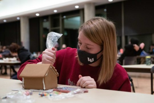 Masked student decorates gingerbread house