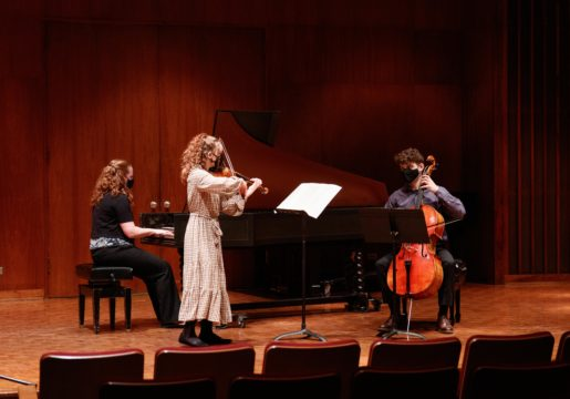 A pianist, violinist, and cellist play together masked on a stage.