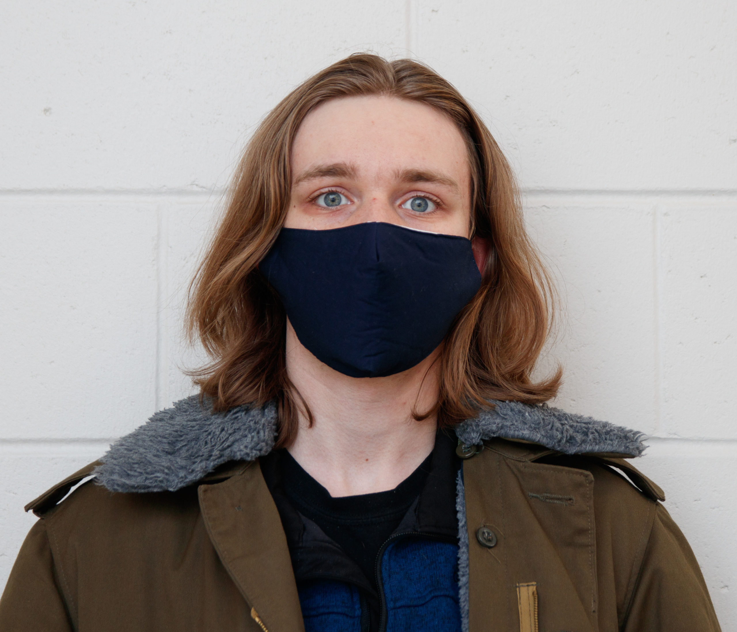 Male presenting person with shoulder length hair in mask wearing coat looks into camera on cement block background.
