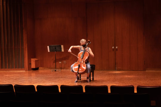 Masked young white person plays cello alone on stage.