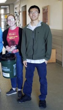 Young woman and man stand in hallway with 5 gallon compost bucket