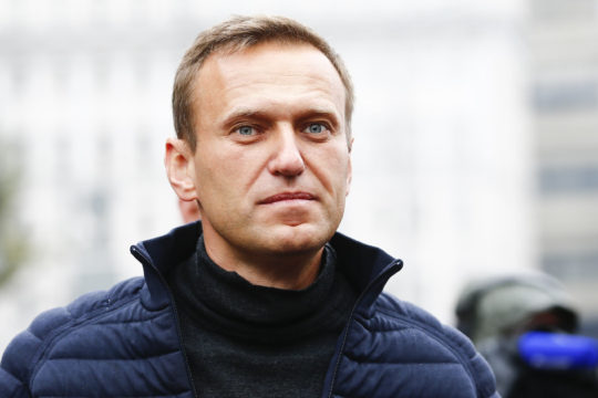 White man with short hair in jacket with turtle neck and puffy coat looks at camera.