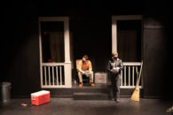Black box stage with a house as the set, young white man sits on a chair on the porch and another young person stands near the steps