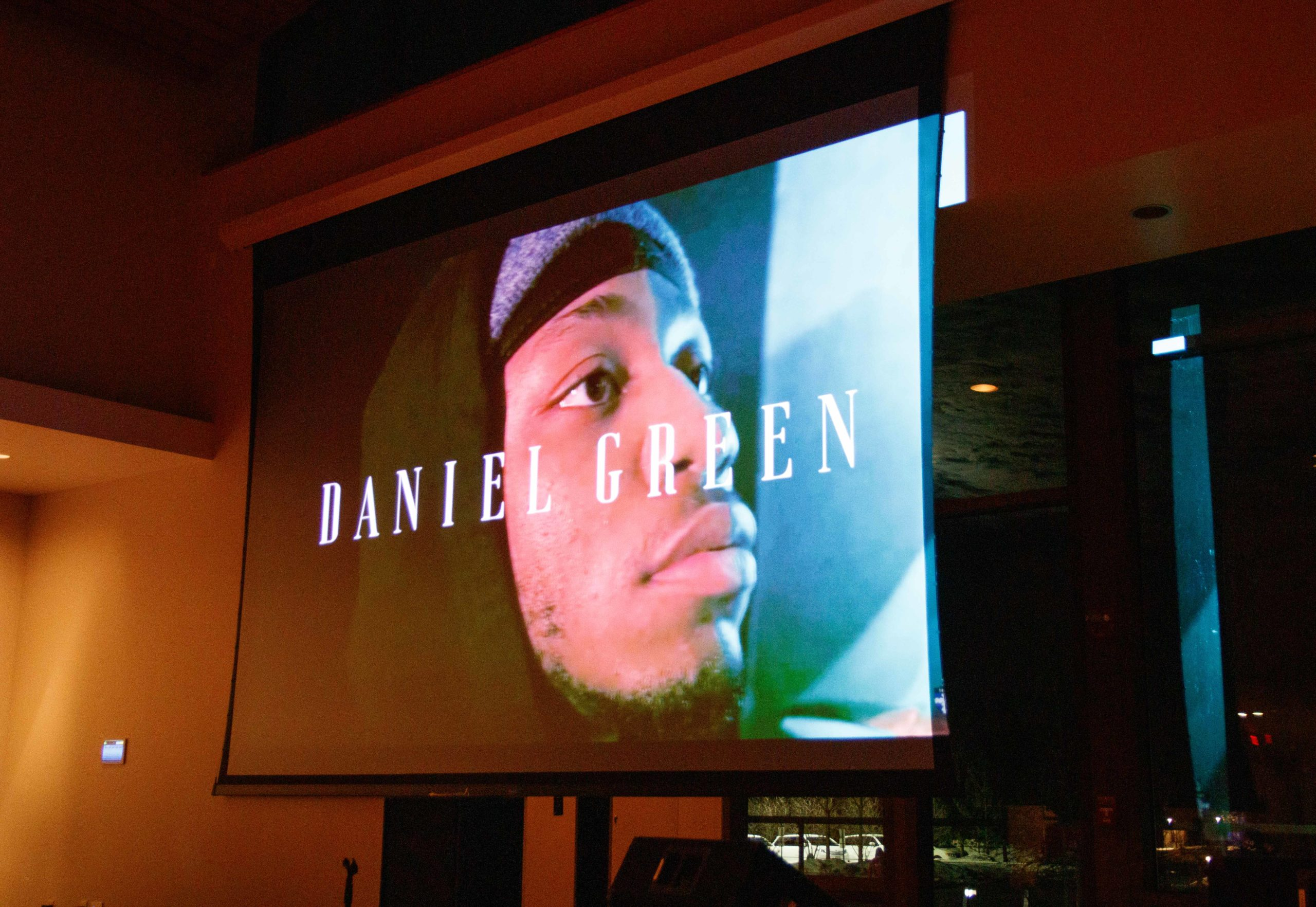 """Projection screen with he words """"DANIEL GREEN"""" on them and a young Black man behind the words"""