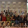 Group of musicians hold their trombones on their heads like hats and pose for a photo.
